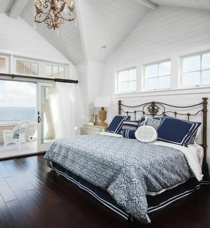 Schlafzimmer mit Meeresblick, blaue Bettwäsche, Decke mit Dachschräge, Maritime Möbel, Boden aus Holz,