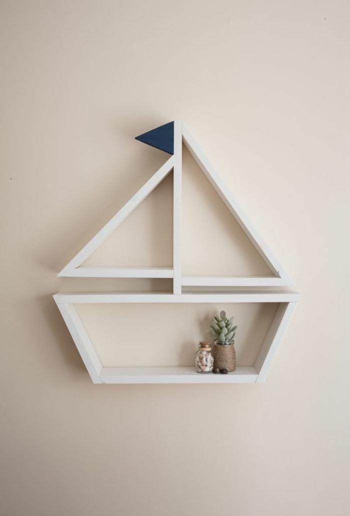 Maritime Wandgestaltung, kleines weißes Segelboot mit blauer Fahne, Einrichtung im maritimen Stil, sehr kleiner Kaktus