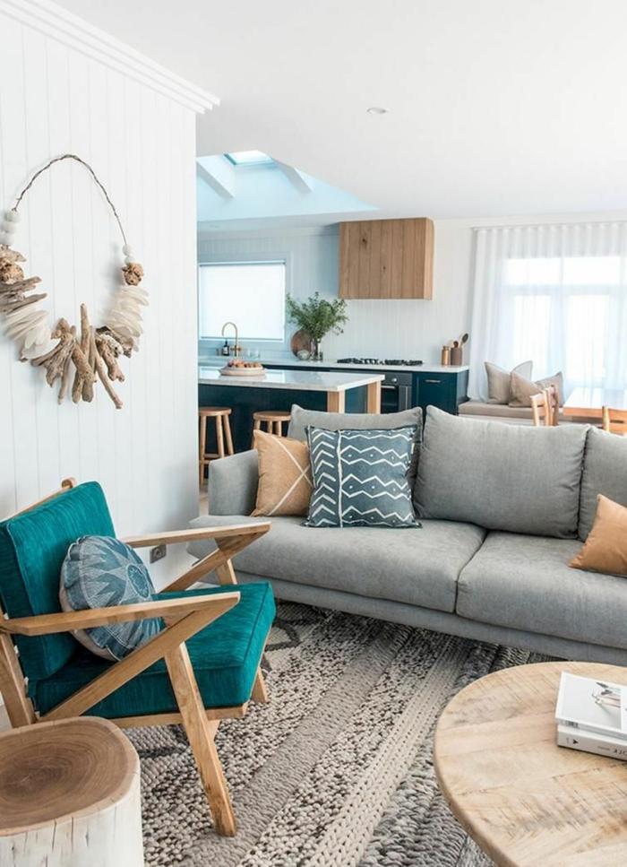 Maritime Wanddeko Treibholz und Muscheln, Sessel in türkis, großes Couch in grau, beiger Teppich, runder Tisch