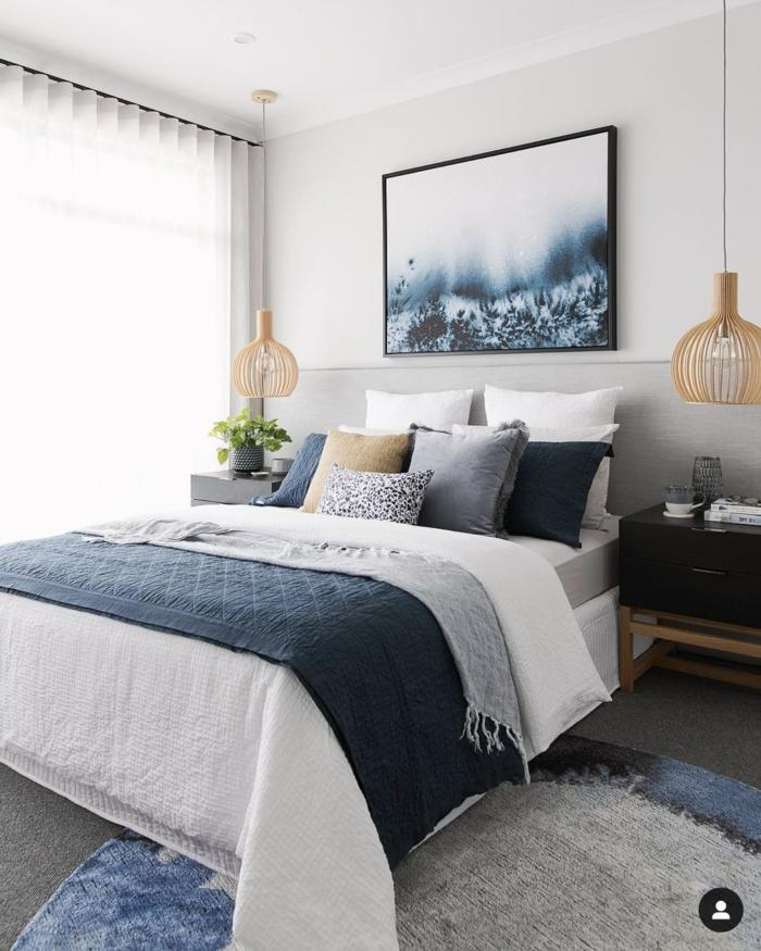 Einrichtung Schlafzimmer im maritimen Stil, maritime Wanddeko, dunkelblaue Bettwäsche und Kissen, Gemälde vom Meeresboden an die Wand,
