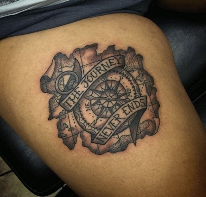 eine weltkarte - idee für einen kleinen tattoo mit einem schwarzen kompass auf der hand