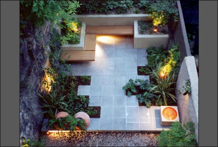 ein minimalistischer Garten mit vielen pflegeleichten Blumenbeeten, eine Sitzecke