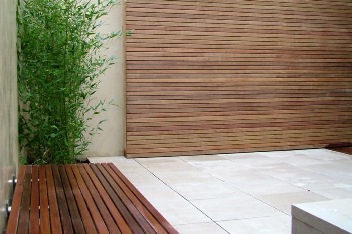 ein Holz Sichtschutz, eine Bank und grüne Pflanze, Fliesen Bodenbeläge - minimalistischer Garten