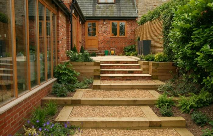 Moderne Gartengestaltung - grüne Pflanzen und Treppe mit Kies bedeckt