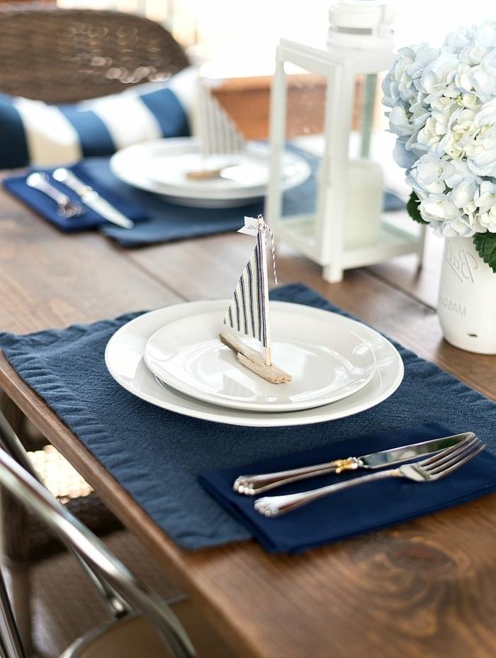 schöne maritime Tischdeko, Segelboot aus Treibholz auf einem weißen Teller, weiße Blumen, Tischset in blau