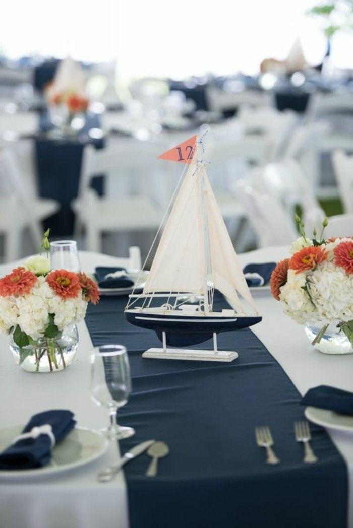 Maritime Tischdeko, orange und weiße Blumen, kleines Segelboot in blau und weiß, blauer Tischläufer, weiße Tischdecke