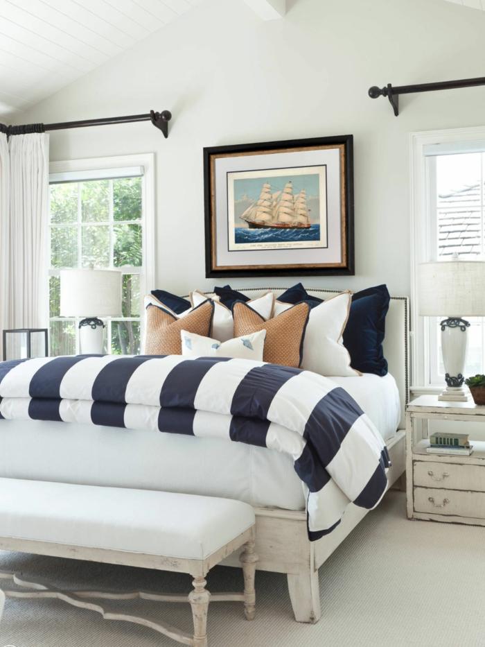 Bilde von einem Segelboot über dem Bett mit braunem Rahmen, gestreifte Bettwäsche in blau und weiß, deko maritim,