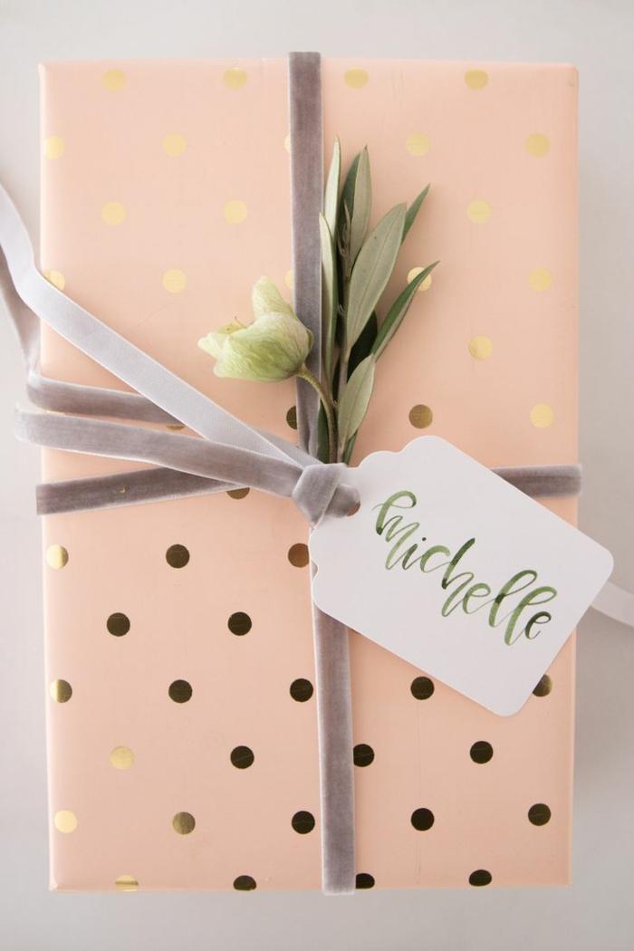 Verpackungsideen ein kleines rosa Geschenk auf Punkten Muster mit einem kleinen Blumen als Deko
