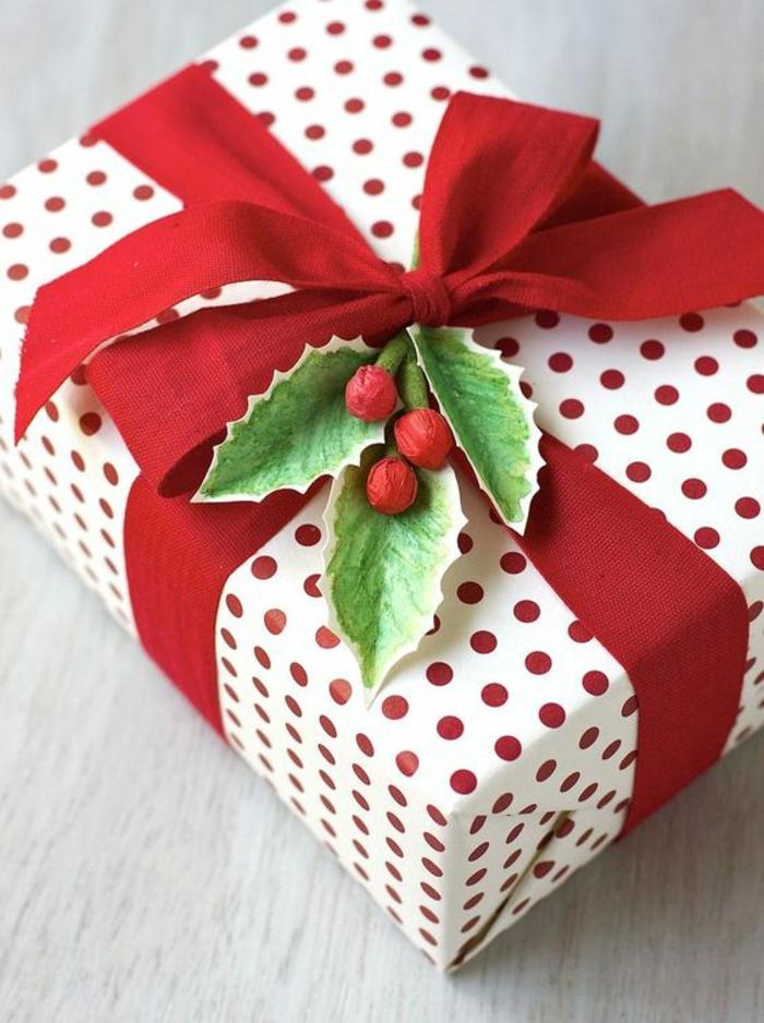 Geschenkverpackung basteln aus schwarzem Band, Geschenkpapier auf rote Punkte und ein grünes Zweig aus Papier