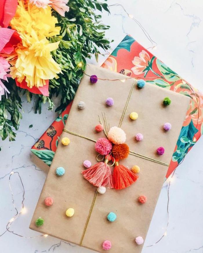 Geschenkverpackungen basteln - mit Pompoms und Bänder bemusterte und nicht bemusterte Geschenkpapier auf zwei Geschenke
