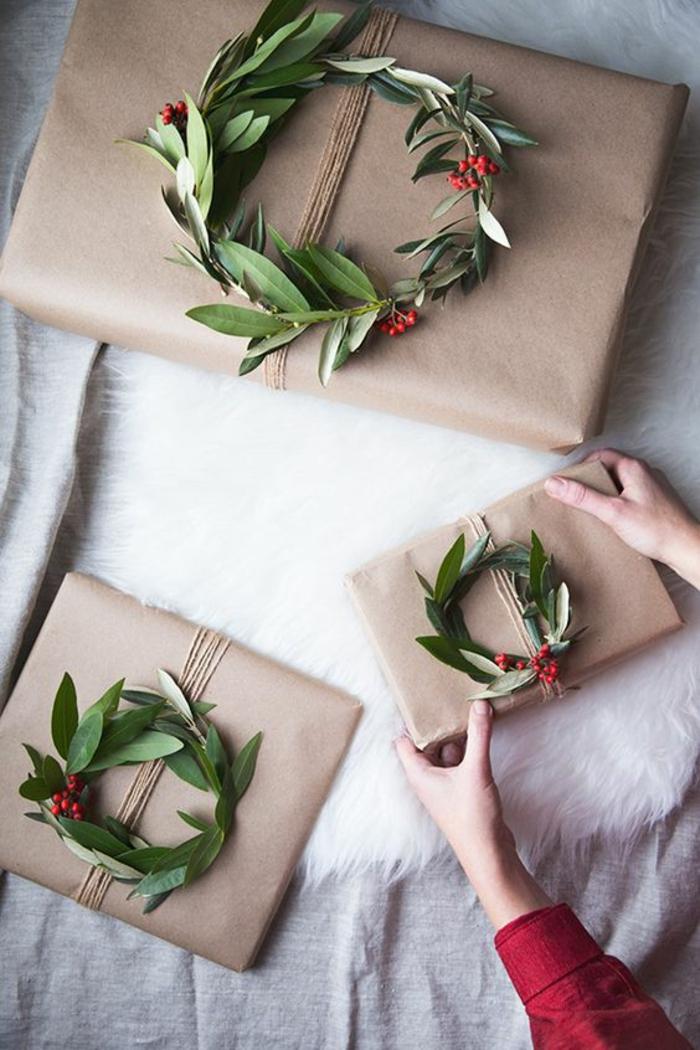 Geschenke kreativ verpacken mit grünen Kränze und rote Früchte als Dekoration