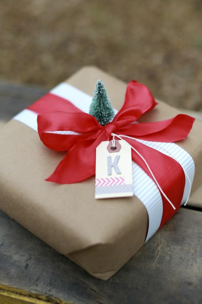 Geschenke kreativ verpacken ein winziger Tannenbaum rotes Band und Karte mit dem Buchstaben