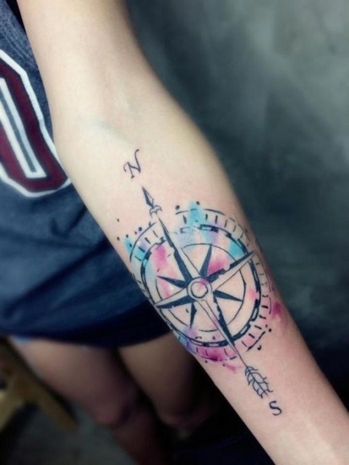 das ist eine der schönsten bunten tätowierungen mit einem großen schwarzen kompass - idee für einen compass tattoo auf der hand einer jungen frau