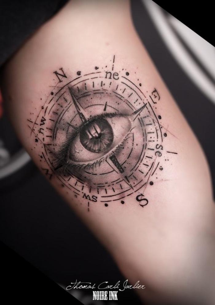 ein großes schwarzes auge und ein großes schwarzes kompass - idee für einen tollen schwarzen tattoo compass auf einer hand