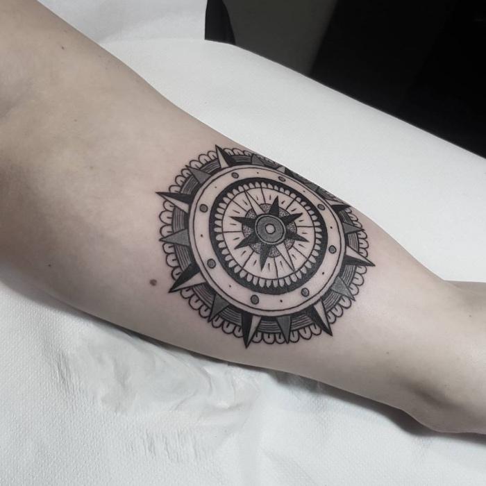 das ist eine unserer ideen für einen kleinen schwarzen tattoo mit rinrm schwarzen mandala kompass auf der hand
