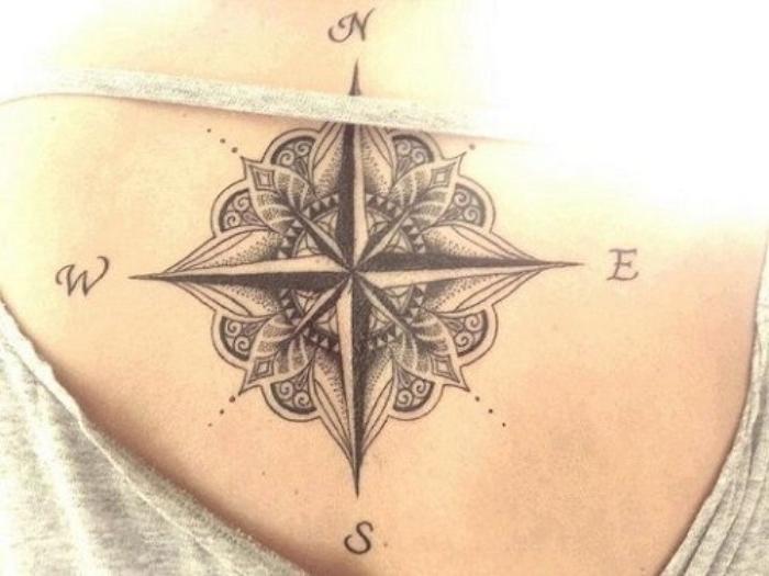 ein schwarzer kompass mit kleinen schwarzen blättern - ein tattoo auf dem rücken einer jungen frau