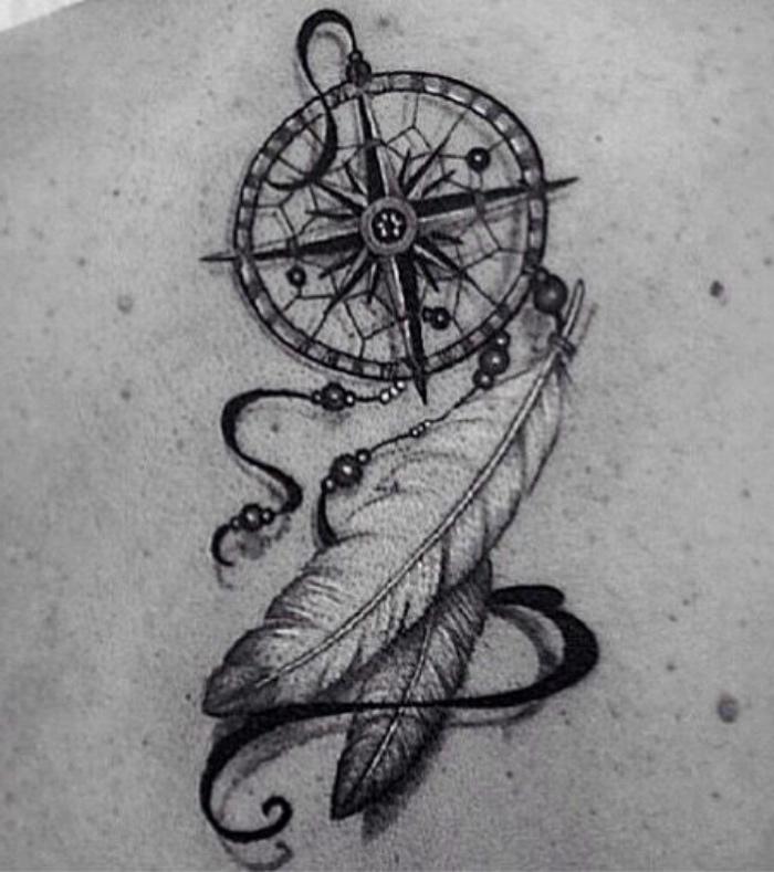 ein schwarzer tattoo mit einem kleinen schwarzen kompass und zwei schönen weißen langen federn