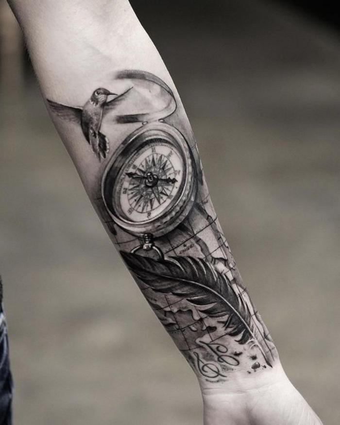 ein vogel, ein schwarzer kompass und eine lange schwarze feder - idee für einen compass tattoo auf der hand