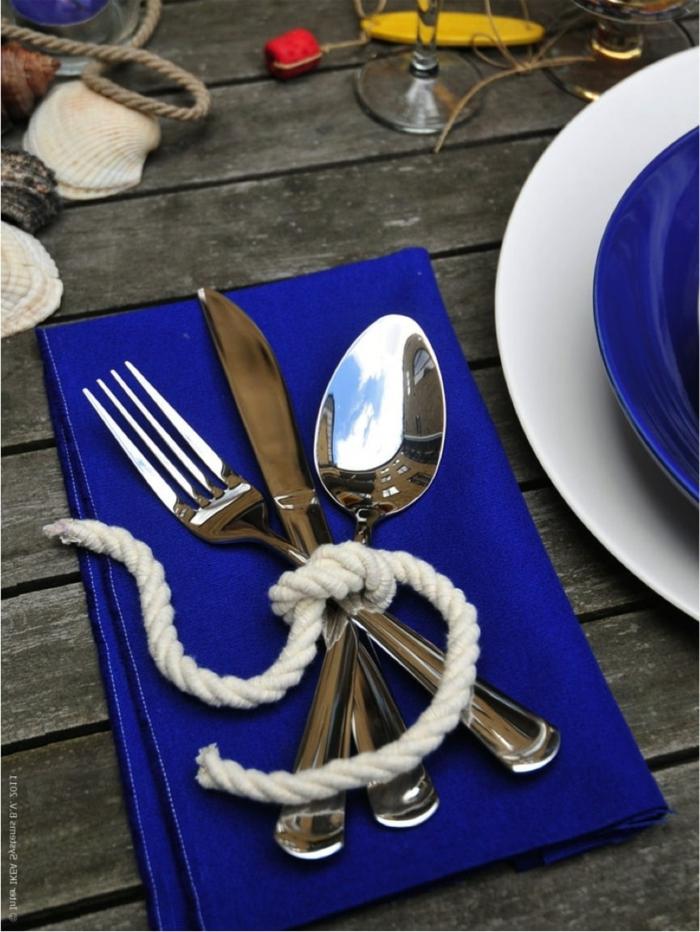 Maritime Dekoration günstig kaufen für Tischdekoration, Besteckt gebunden, mit weißem Seil, Serviette in Blau, Muscheln im Hintergrund