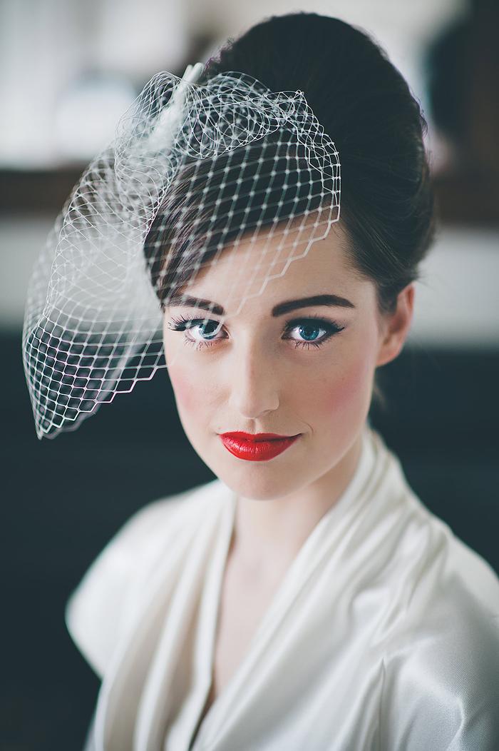 schwarze Haare ein Schleier Hochsteckfrisur Hochzeit roter Lippenstift weißes Kleid