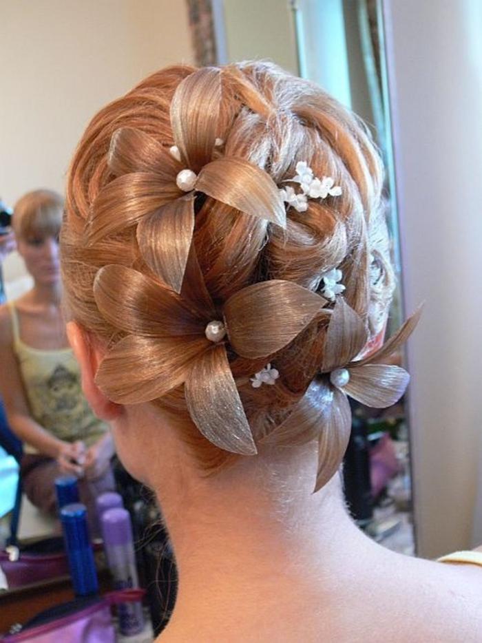 eine ausgefallen Hochzeit Frisur mit Blumen in der Farbe von dem Haar