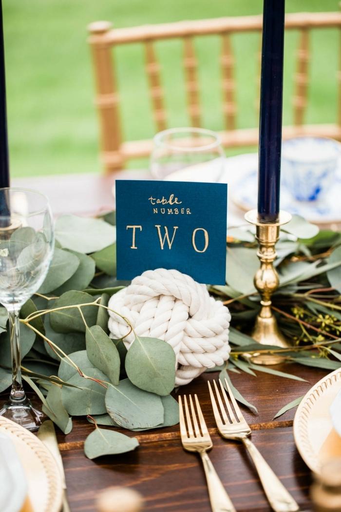 Maritime Tischdeko Hochzeit, Holztisch dekoriert mit grünen Blättern, weißer Knotenball, große blaue Kerze