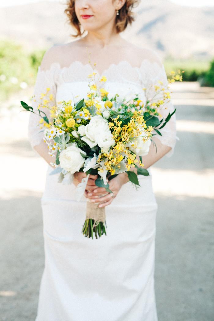 schöne weiße Hochzeitskleid, gelbe Blumen und weiße Rosen in vintage Brautstrauß
