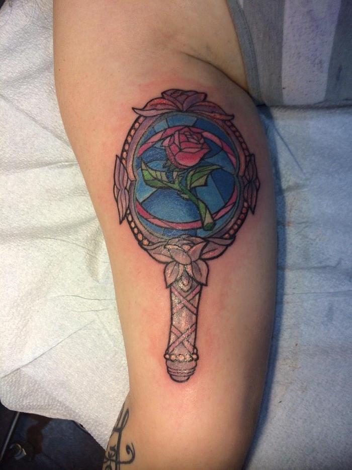 tattoo rose mit märchenhaften motiven die schöne und das biest - ein spiegel und eine rote rose mit grünen blättern
