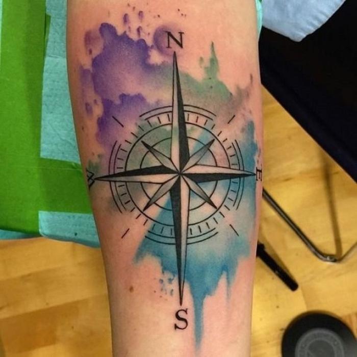 ein schöner schwarzer großer tattoo mit einem schwarzen kompass - eine hand mit einem compass tattoo und bunten farben