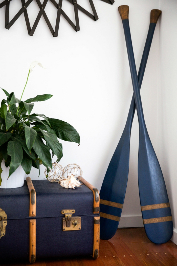 Inneneinrichtung Wohnzimmer maritimer Stil, zwei große Ruder in blau, große Truhe in dunkelblau, grüne Pflanze