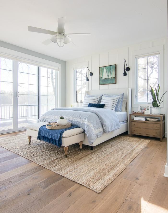 großes Schlafzimmer maritim, großes Bett mit blauen Bettwäschen, gemaltes Bild von einem Segelboot, hellbrauner Teppich, Kommode aus Holz