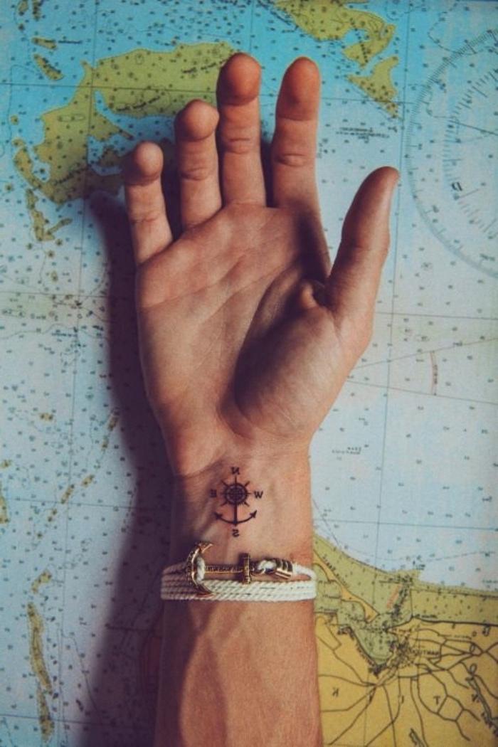 die weltkarte, ein schwarzer kleiner anker und ein schwarzer kleiner kompass - idee für einen compass auf dem handgelenk