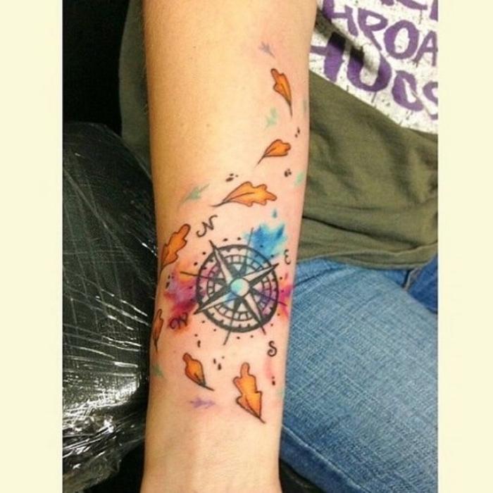 das ist eine idee für eine schöne bunte tätowierung mit orangen blättern und einem schwarzen kompass - eine hand mit compass tattoo