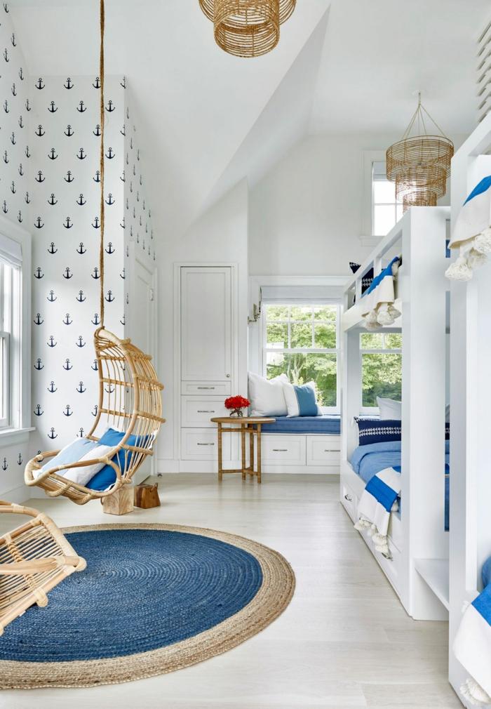 Kinderzimmer mit Etagenbetten, runder Teppich maritim, blaue Decken und Kissen, weiße Tapete mit Anker