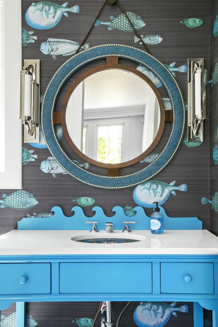 Badezimmer deko maritim, großer runder Spiegel, aufgeklebte Fische an die Wand, blauer Waschbecken mit Schränke