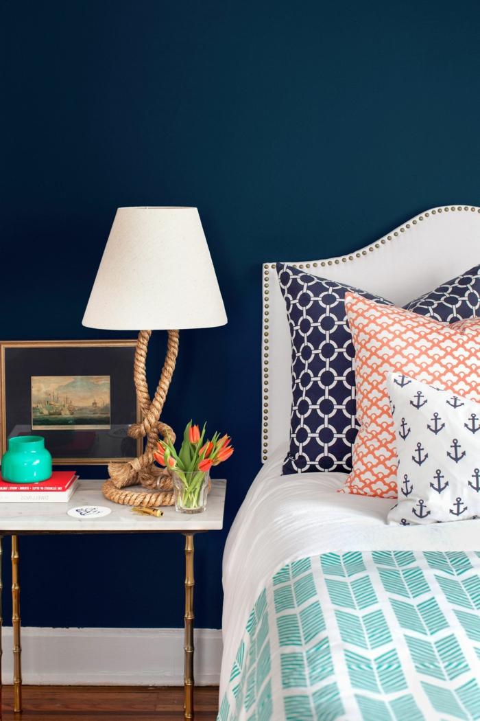 Schlafzimmer maritim, dunkelblaue Wand, Bettwäsche mit maritimen Motiven, weiße Lampe mit langem Seil
