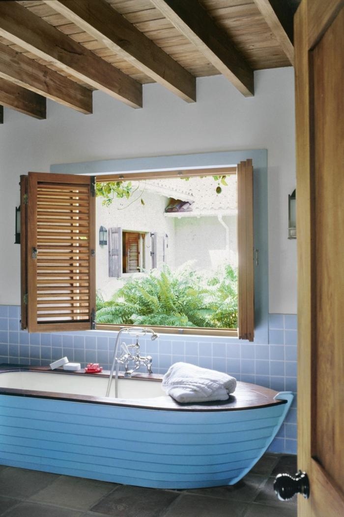 Einrichtung Maritime Badezimmer, Badewanne wie ein Segelboot in hellblau, blaue Fliesen, Holzdach und Holzfenster
