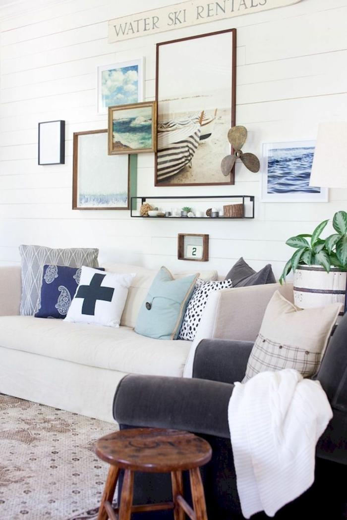 Wohnzimmer mit maritimer Dekoration, maritime Wanddeko mit Bildern vom Meer, blauer Sessel, Couch in beige, Kissen im nautischen Stil