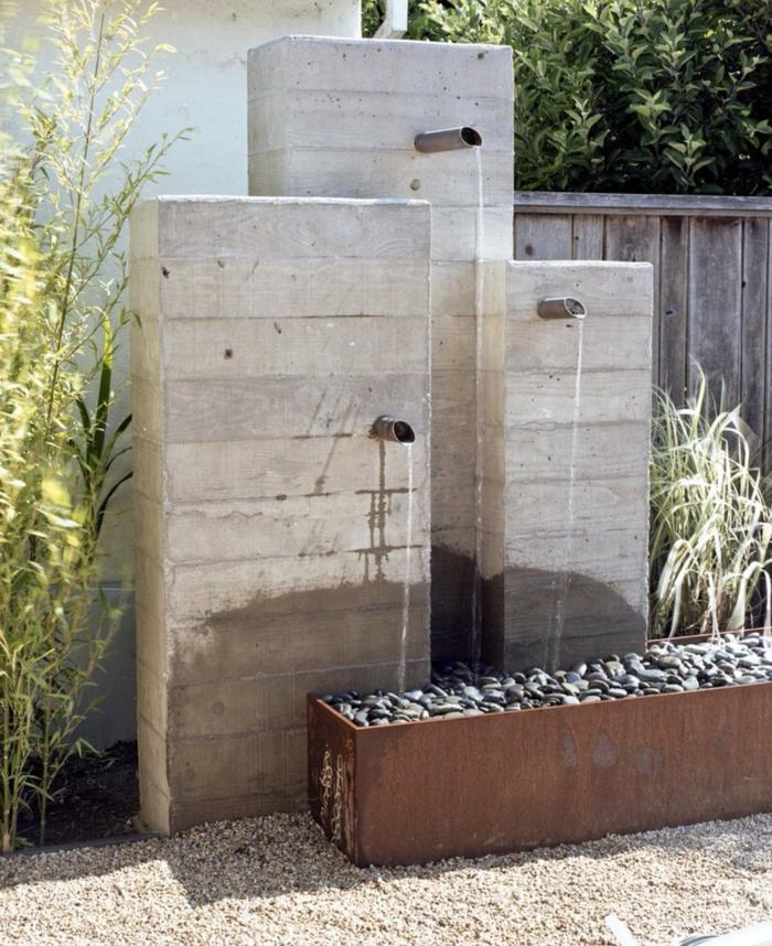 drei Hähnen die auf Steinen fließen grüne Pflanzen - puristischer Garten