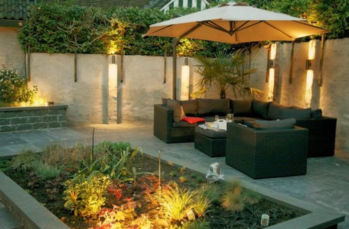 puristischer Garten - gut beleuchteter Garten mit vielen grünen Pflanzen und schicke Gartenmöbel