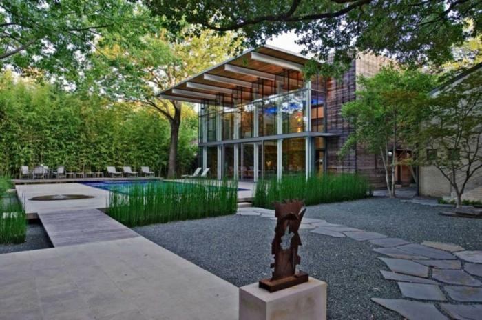 ein Haus mit einem modernen Vorgarten, Glasfassade, ein Schwimmbad, Skulptur