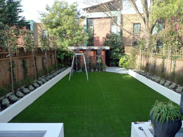 zwei symmetrische Reihen von Pflanzen an dem Zaun, grüner Rasen - moderner Vorgarten