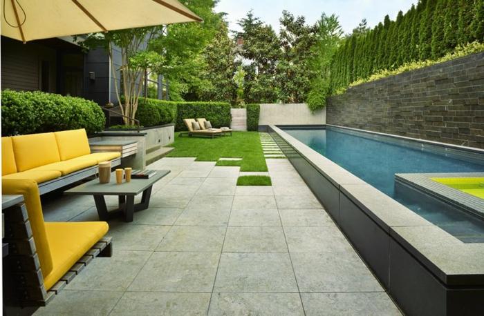 grüner Rasen Liegestühle gelbe Gartenmöbel ein Schwimmbad puristischer Garten