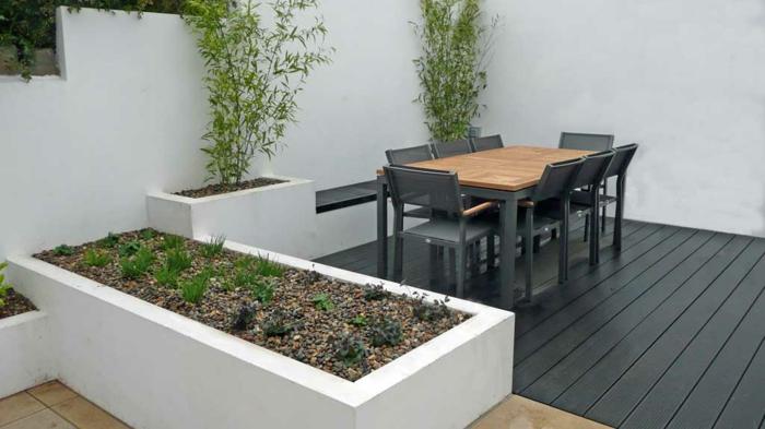 ein Beet in grüner Farbe, zwei Ziersträucher, schicke Gartenmöbel - puristischer Garten
