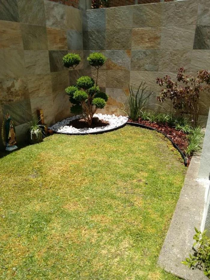 Gartengestaltung modern - Zierbaum in der Ecke, grüner Rasen, kleine weiße Steine