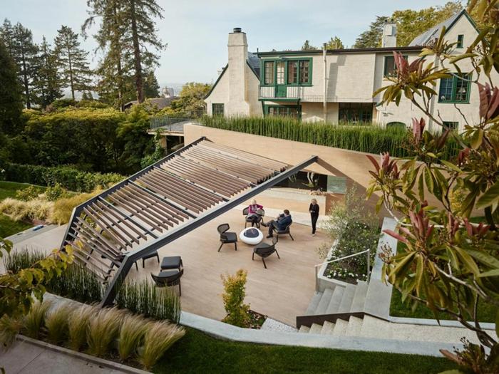 ein Pergola, gepflegtes hohes Gras, Gartenmöbel und Haus in minimalistischem Stil - moderne Vorgärten