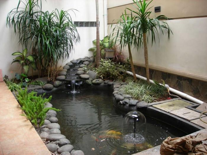 ein schönes Wasserspiel mit vielen grauen Steinen und exotische Palmen - Gartengestaltung Beispiele