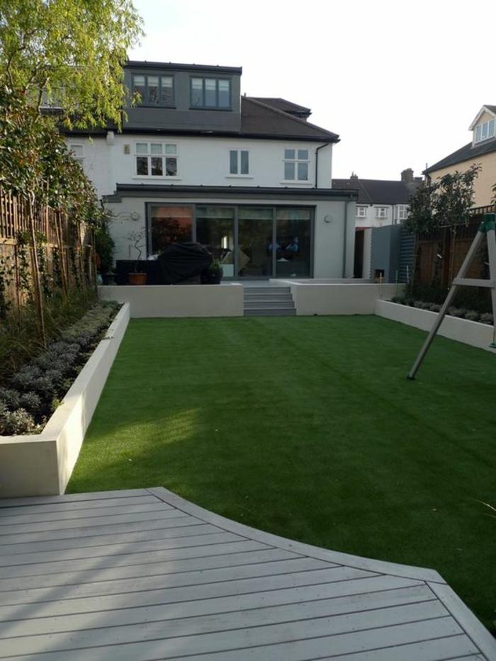 ein künstlicher Gras Rasen, Bäume an den Zaun, Haus im minimalistischem Stil - Gartengestaltung Beispiele