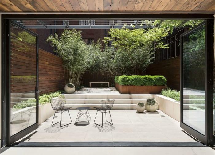 ein kompakter moderner Vorgarten, der alles in sich enthält - Blumenbeete und Gartenmöbel