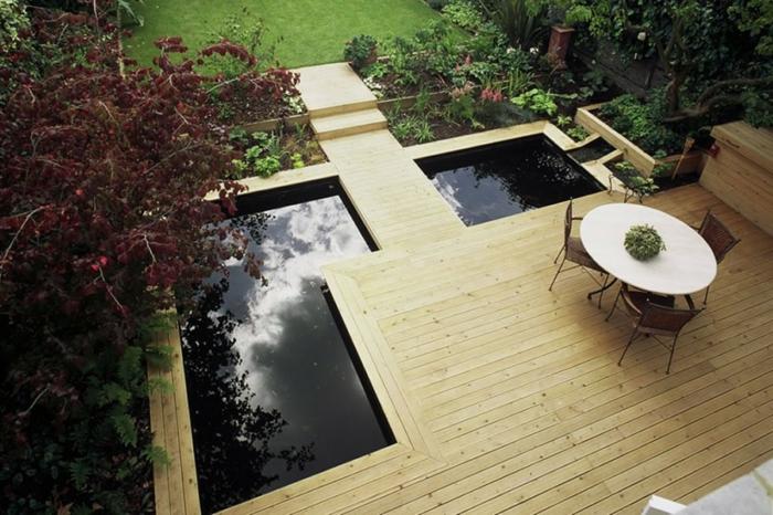 ein moderner Vorgarten in Foto von oben - Teich und Gartenmöbel, grüne Pflanzen